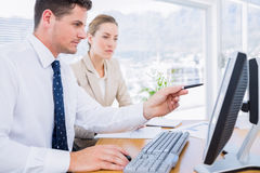 Smartly dressed colleagues using computer Stock Image