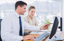 Smartly dressed colleagues using computer Stock Photo