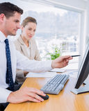 Smartly dressed colleagues using computer Stock Photography