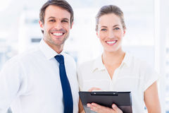 Smartly dressed colleagues using digital tablet Royalty Free Stock Photos