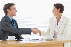 Smartly dressed couple shaking hands in business meeting Stock Image