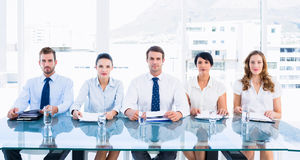 Smartly dressed executives sitting in row at desk. Portrait of smartly dressed young executives sitting in row at desk in a bright office royalty free stock photography