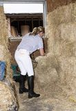 Woman in a stable filling a hay net with feed for her horse. Smartly dressed horse rider filling a haynet to feed a horse. November 2017 Stock Image