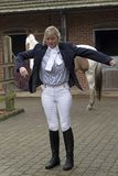 Woman horse rider getting dressed in a blue jacket. Smartly dressed horse rider putting on a dark blue riding jacket, November 2017 Royalty Free Stock Photography