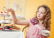 Smartly dressed little girl drinking tea with cake Stock Photography
