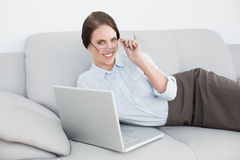 Smartly dressed smiling woman with laptop on sofa Stock Images