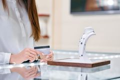 Woman is holding credit card in her hands and standing near the necklace in a jewelry shop. Smartly dressed woman in a chic white blouse is holding credit card Stock Photos