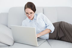 Smartly dressed woman using laptop on sofa Stock Photo
