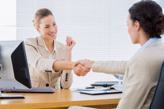 Smartly dressed women shaking hands in business meeting. Smartly dressed young women shaking hands in a business meeting at office desk Royalty Free Stock Photography