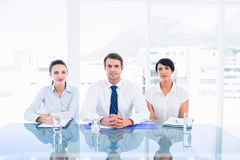 Smartly dressed young executives sitting at desk Stock Photography