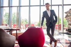 Smartly klädd affärsman som ler att stå i regeringsställning arkivbild