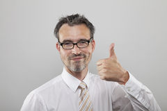 Smartly smiling office clerk. Holds his thumb up stock images