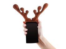 Smartphon圣诞节滑稽的概念,驯鹿鹿角在白色戏弄,隔绝 免版税图库摄影