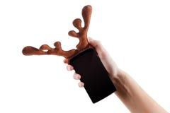 Smartphon圣诞节滑稽的概念,驯鹿鹿角在白色戏弄,隔绝 免版税库存照片