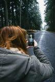 Smartphone à disposição na estrada do inverno do fundo nas madeiras fotos de stock royalty free