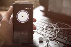 Smartphone à disposition, écouteurs, ordinateur portable, multimédia image stock