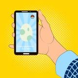 Smartphone à disposition avec l'image du jeu d'oeufs Photo libre de droits