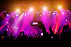 Smartphone à disposition à un concert, lumière pourpre d'étape photo stock