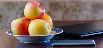 Smartphone, Äpfel auf einer Platte und einem Laptop Gesunder Bruch Lizenzfreies Stockbild
