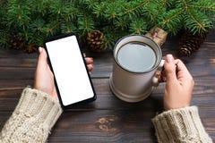 Smartphone åtlöje upp kvinnahänder som rymmer koppen av den varma bästa sikten för kaffe och för telefon på träbakgrund med julga royaltyfria bilder
