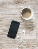 Smartphone, écouteurs, carnet et café sur le fond en bois Photographie stock libre de droits
