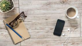 Smartphone, écouteurs, carnet et café sur le fond en bois Images libres de droits