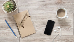 Smartphone, écouteurs, carnet et café sur le fond en bois Image libre de droits