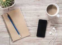 Smartphone, écouteurs, carnet et café sur le fond en bois Photographie stock