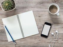 Smartphone, écouteurs, carnet et café sur le fond en bois Images stock