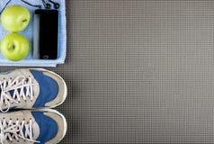 Smartphone, écouteurs, pomme sur la serviette bleue et espadrilles sur le tapis Image stock