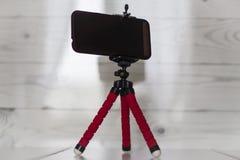 Smartphone σε ένα κόκκινο τρίποδο σε ένα άσπρο υπόβαθρο κουζινών στοκ φωτογραφίες με δικαίωμα ελεύθερης χρήσης
