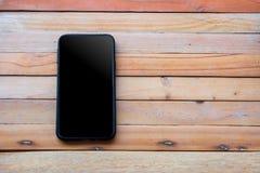 Smartphone στο ξύλινο υπόβαθρο χρησιμοποίηση της ταπετσαρίας για την εκπαίδευση, επιχειρησιακή φωτογραφία Σημειώστε το προϊόν για στοκ φωτογραφία