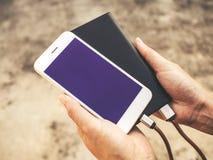 Smartphone ładuje bateria od zewnętrznie władzy banka zdjęcia royalty free
