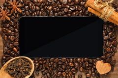 Smartphone ή ταμπλέτα με το πλαίσιο των φασολιών και των καρυκευμάτων καφέ στοκ φωτογραφία με δικαίωμα ελεύθερης χρήσης