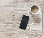 Smartphone, ακουστικά, σημειωματάριο και καφές στο ξύλινο υπόβαθρο Στοκ Φωτογραφίες