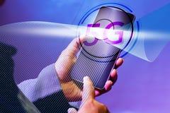 Smartphone αφής με το δάχτυλο δεικτών για, που απομονώνεται στο εικονίδιο 5G και τη ροή κυμάτων στην εικονική έννοια οθόνης Επιχε στοκ εικόνα