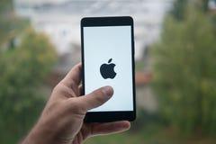 Smartphone εκμετάλλευσης ατόμων με το λογότυπο της Apple με το δάχτυλο στην οθόνη Στοκ Φωτογραφία