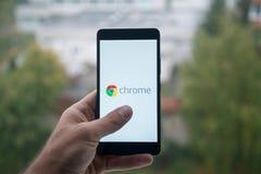 Smartphone εκμετάλλευσης ατόμων με το χρώμιο Google με το δάχτυλο στην οθόνη στοκ φωτογραφίες