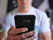 Smartphone εκμετάλλευσης ατόμων/τηλέφωνο κυττάρων υπό εξέταση με την κενή οθόνη στοκ εικόνα