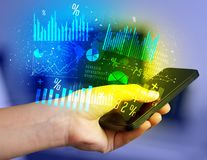 Smartphone εκμετάλλευσης χεριών με τα επιχειρησιακά διαγράμματα Στοκ εικόνες με δικαίωμα ελεύθερης χρήσης