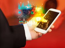 Smartphone εκμετάλλευσης χεριών με τα επιχειρησιακά διαγράμματα Στοκ Φωτογραφίες