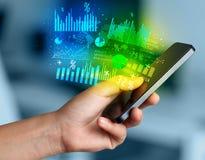 Smartphone εκμετάλλευσης χεριών με τα επιχειρησιακά διαγράμματα Στοκ Εικόνα