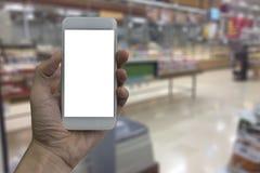 Smartphone εκμετάλλευσης χεριών με την άσπρη κενή οθόνη πέρα από τη θολωμένη γουλιά Στοκ Φωτογραφίες