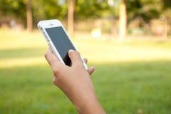 Smartphone εκμετάλλευσης χεριών γυναικών Στοκ Εικόνες