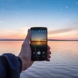 smartphone εκμετάλλευσης χεριών και λήψη μιας φωτογραφίας του ηλιοβασιλέματος Στοκ φωτογραφίες με δικαίωμα ελεύθερης χρήσης