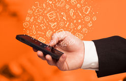 Smartphone εκμετάλλευσης χεριών με συρμένα τα χέρι εικονίδια και τα σύμβολα μέσων Στοκ εικόνα με δικαίωμα ελεύθερης χρήσης