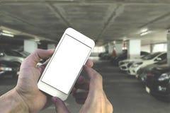 Smartphone εκμετάλλευσης χεριών με την άσπρη κενή οθόνη πέρα από τη θολωμένη ισοτιμία Στοκ Εικόνα