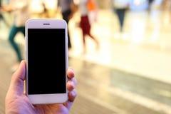 Smartphone εκμετάλλευσης χεριών με το υπόβαθρο σταθμών μετρό Στοκ φωτογραφία με δικαίωμα ελεύθερης χρήσης