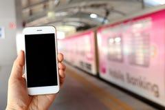 Smartphone εκμετάλλευσης χεριών με το υπόβαθρο σταθμών μετρό Στοκ εικόνες με δικαίωμα ελεύθερης χρήσης