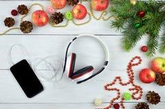 Smartphone και ακουστικό με τις αγροτικές διακοσμήσεις Χριστουγέννων Chr Στοκ εικόνες με δικαίωμα ελεύθερης χρήσης
